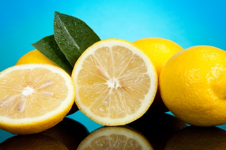 citrons: yellow  lemons with green leaves on blue background Stock Photo