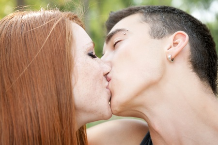 young caucasian couple kissing,  side view, close-up photo