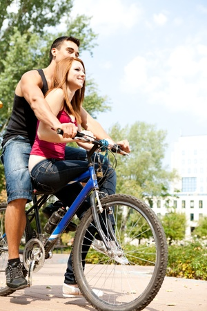 excited young love couple riding a bicycle in a park - having fun outdoor Stock Photo - 10975139