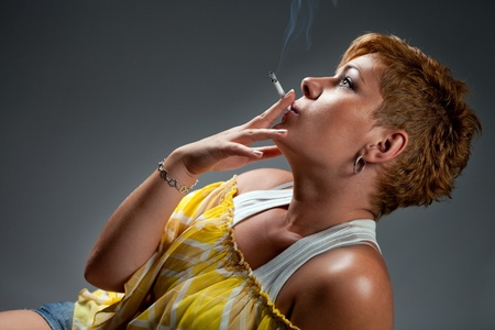 elegant woman smoking cigar on gray background photo