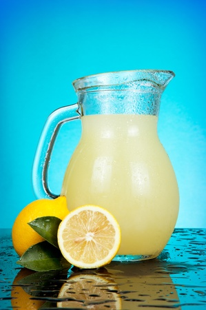 fresh cold lemonade in pitcher on blue background photo
