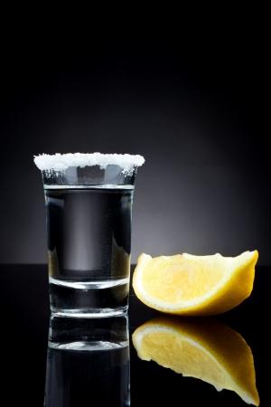 sparo: tequila girato con una fetta di limone su sfondo nero