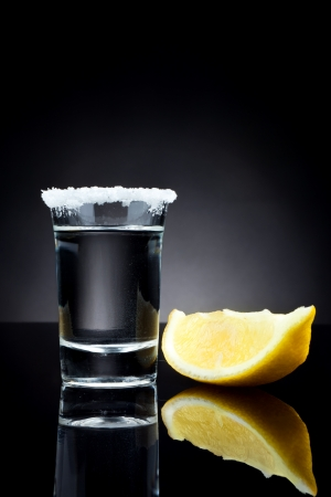 by shot: tequila shot with lemon slice on black background