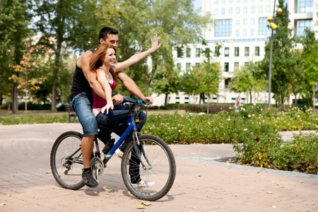 smiling young couple having fun with bicycle, outdoor photo