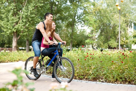 young lovers riding a bicycle, outdoor photo