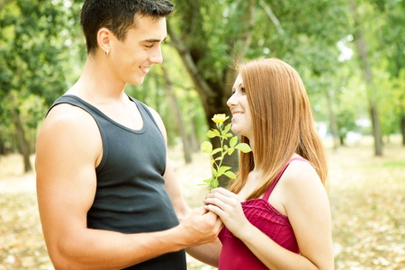 young romantic couple with flower, outdoor photo