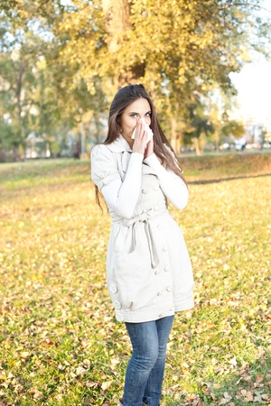 young woman with allergy or cold blowing her nose, outdoor  photo