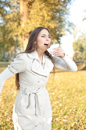 woman with tissue sneezes, outdoor photo