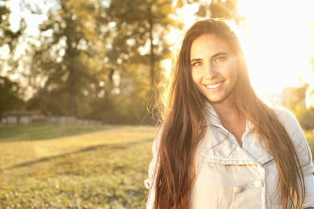 Beautiful woman in a grassy field outdoor backlit by sunlight photo