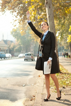 hailing: Business woman hailing  taxi cab in city