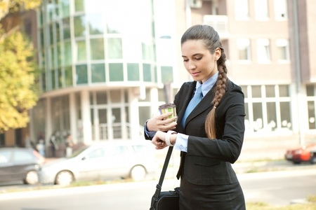 cheerful,  busy businesswoman checking the time, outdoor photo