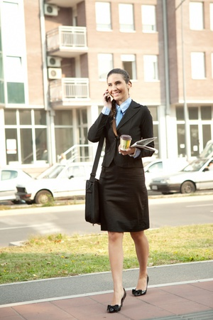businesswoman walking on street of urban city photo