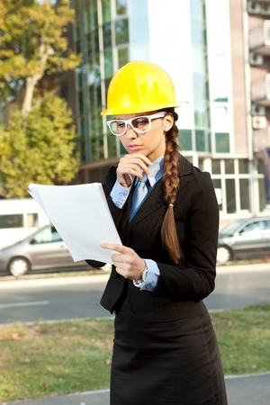 Woman in yellow hard hat,  reading notes while standing photo