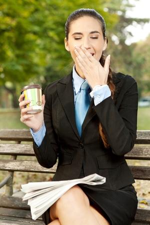 cansancio: mujer de negocios cansada que bosteza en las vacaciones de cafetería en el parque