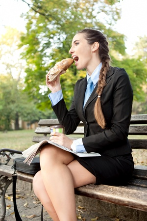 hungry businesswoman eating roll pastry in park photo