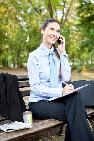 businesswoman working  and using mobile phone in park photo