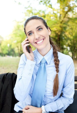 young, smiling business woman on phone in the park in vertical composition photo