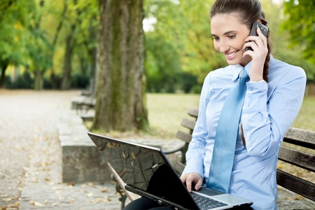 beautiful businesswoman using phone and laptop in park photo