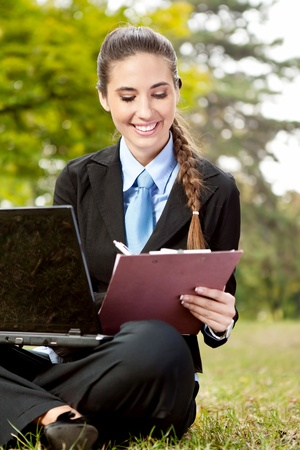 young businesswoman in suit working on grass, making note photo