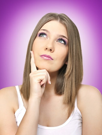 portrait of young thinking blond girl on violet background photo