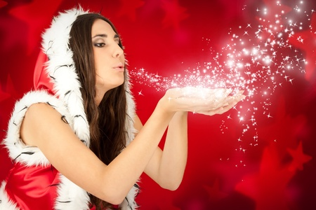 santa girl blowing snow from her hand on red background photo
