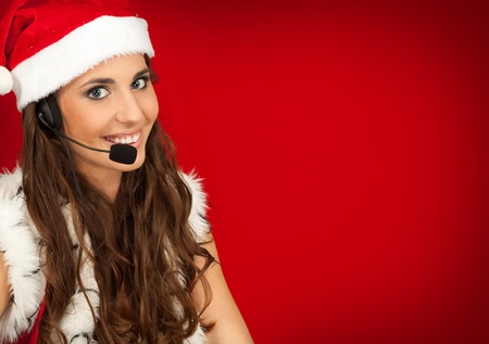 cheerful santa  assistant with headset on red background photo