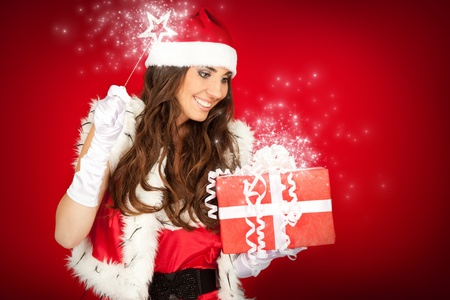 young beautiful Christmas fairy with magic wand and Christmas present photo