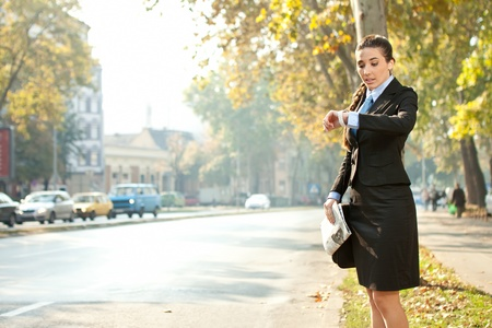 running late: businesswoman looking in watch,  late for work or a meeting Stock Photo