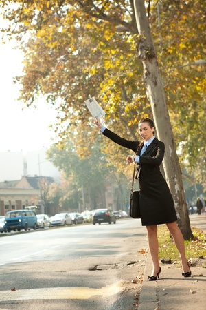 hailing: Businesswoman hailing taxi and looking in clock