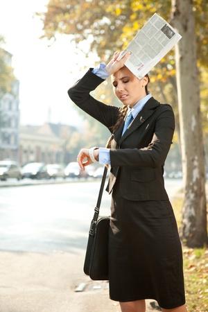 zakenvrouw is te laat voor het werk of een vergadering, op zoek in horloge