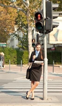 pedestrian crossing: pedestrian businesswoman reading the newspaper next the traffic light Stock Photo