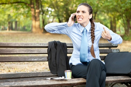 angry businesswoman  on mobile phone, facial expression with gestures ,  outdoor photo