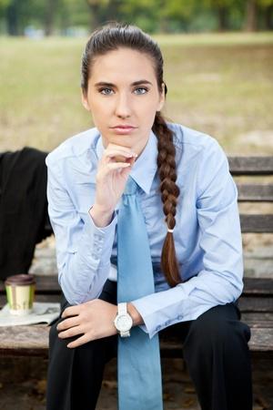 portrait of beautiful businesswoman, sitting in park photo