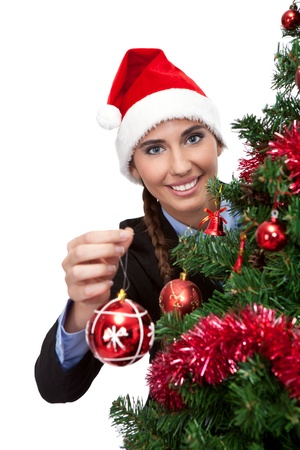 Girl in santa hat holding christmas ball, isolated on white background photo