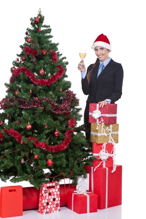 Woman in a christmas hat drink a champagne near a christmas tree, isolated on white background photo