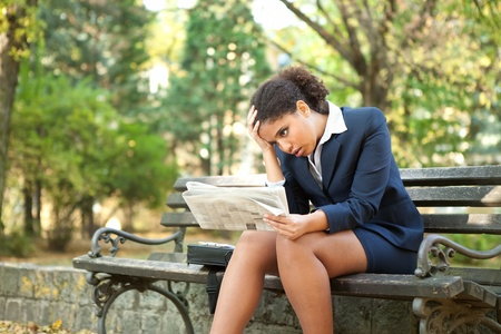 upset , afro businesswoman with newspaper, bad news Stock Photo - 11270939