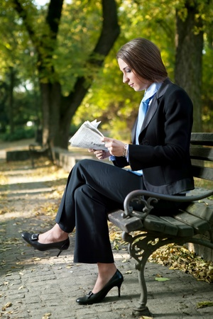 businesswoman reading newspaper on break,  outdoor photo