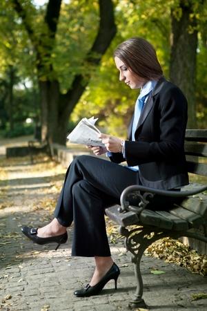 newspaper reading: businesswoman reading newspaper on break,  outdoor