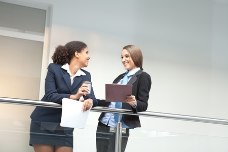 Two smiling attractive young businesswomen chatting on coffee break, indoor Stock Photo - 11270850