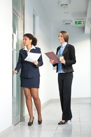 Two attractive business women walking in the office corridor   photo