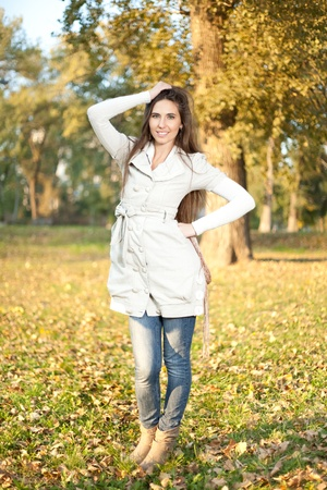 A outdoor portrait of a beautiful young woman with long-haired, posing in a park in late fall photo