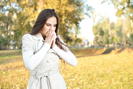 Sick woman with a cold blowing into tissue, outdoor photo
