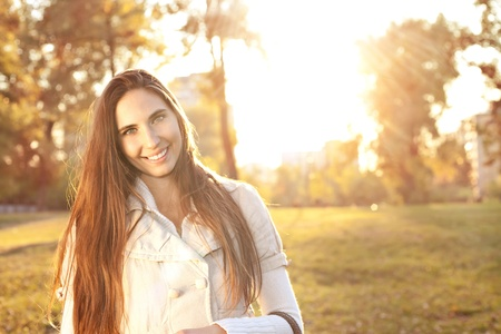 Young beautiful woman in an autumn park with sunlight photo