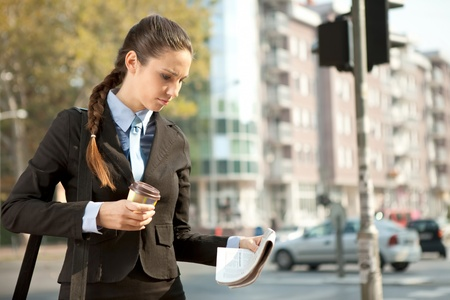 businesswoman with coffee reading newspaper, standing on street  photo