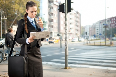 serious businesswoman reading newspaper, outdoor photo