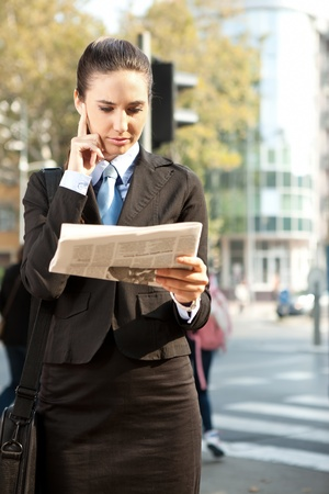 Young business woman in suit reading a newspaper, outdoor photo