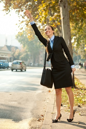 hailing: young businesswoman on street trying to hail taxi cab