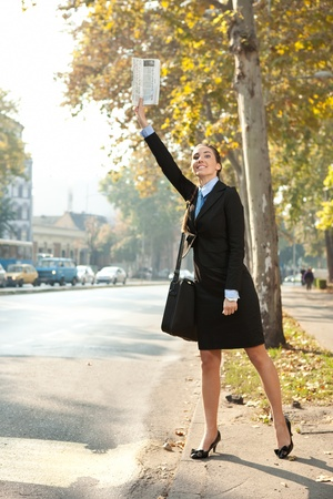 hailing: A young businesswoman trying to hail a cab in the city