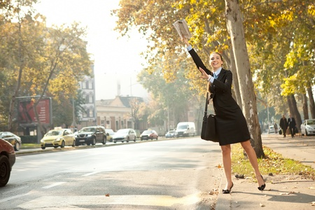 hailing: Businesswoman trying to hail a cab in the city  Stock Photo
