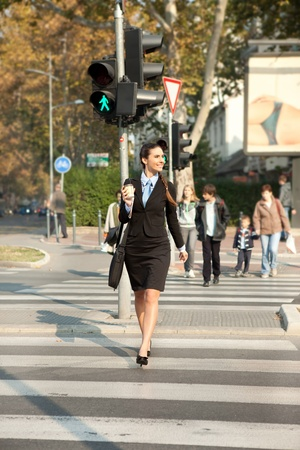 smiling young businesswoman walking on street with coffee in hand photo